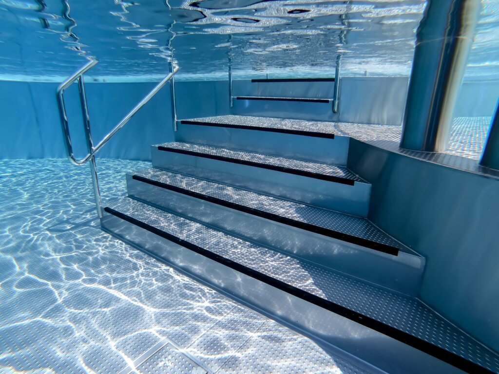 Priame schody do nerezového bazéna - záber pod vodou